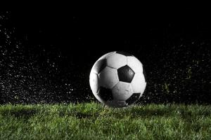 Soccer ball in motion over grass
