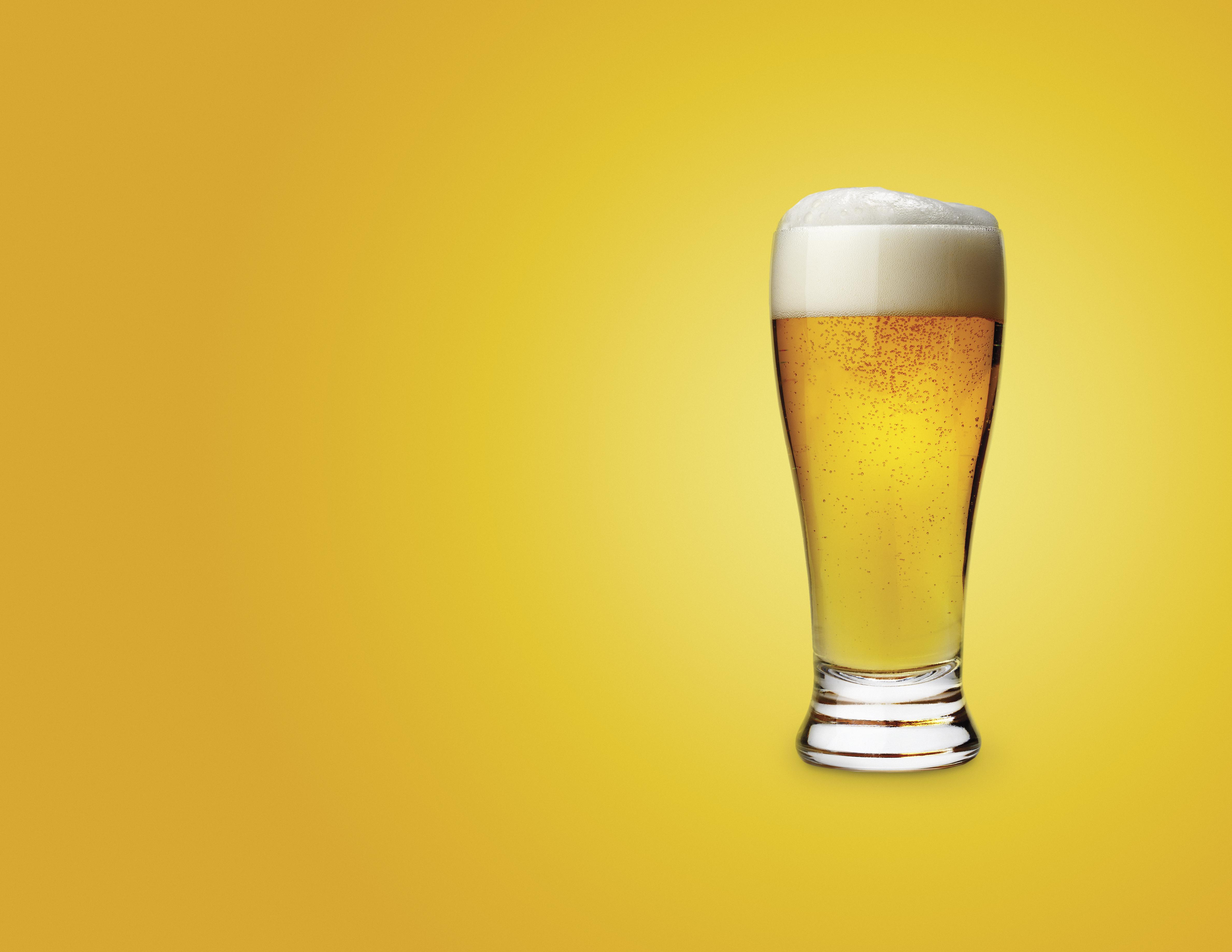 Glass of beer on colored background