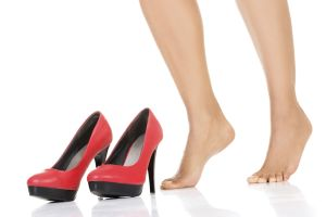 Female legs and red heels. Isolated on white.