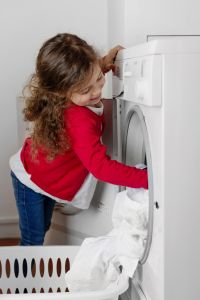 Blond little girl filling tumble dryer with laundry