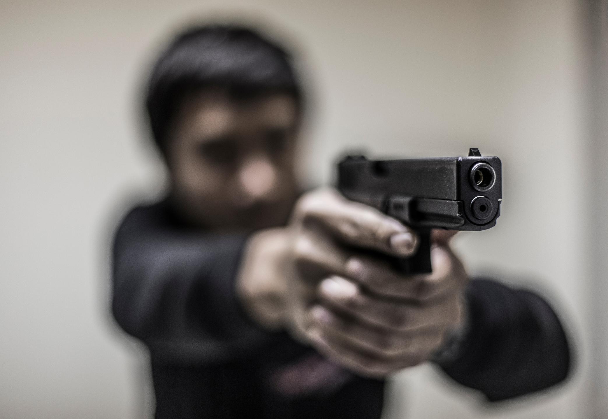 Man Aiming With Gun Against Wall