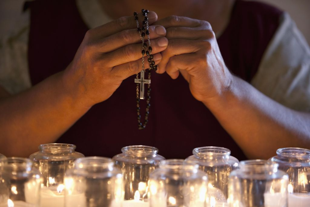 Hands holding prayer beads over candles