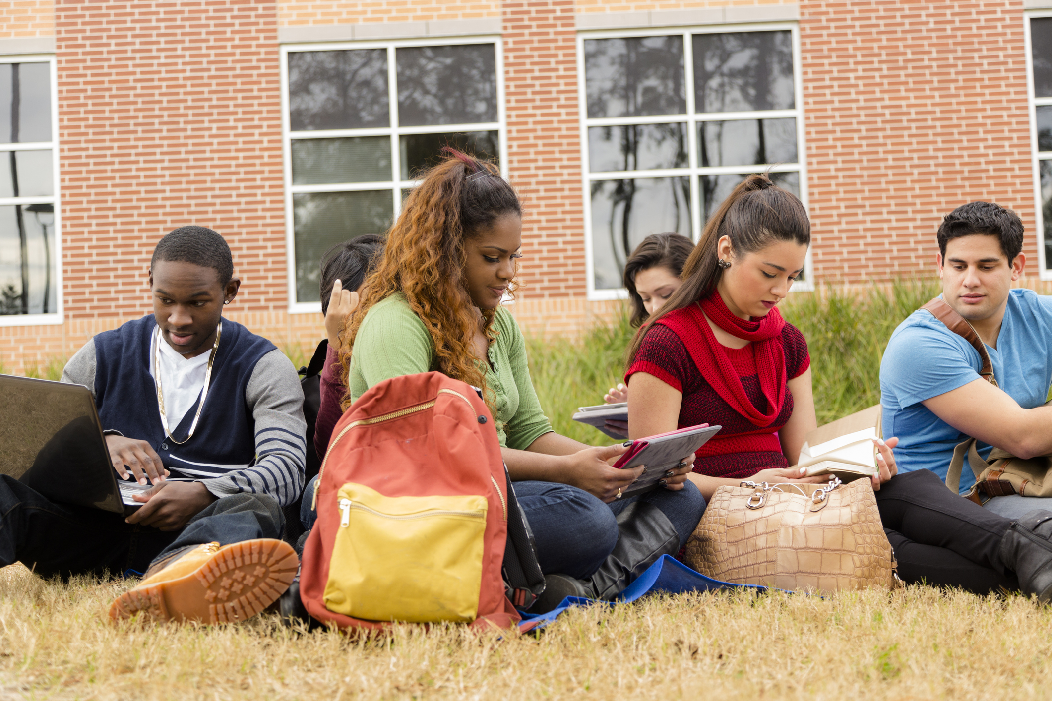 Multi-ethnic group of college student friends. Digital tablet, laptop.