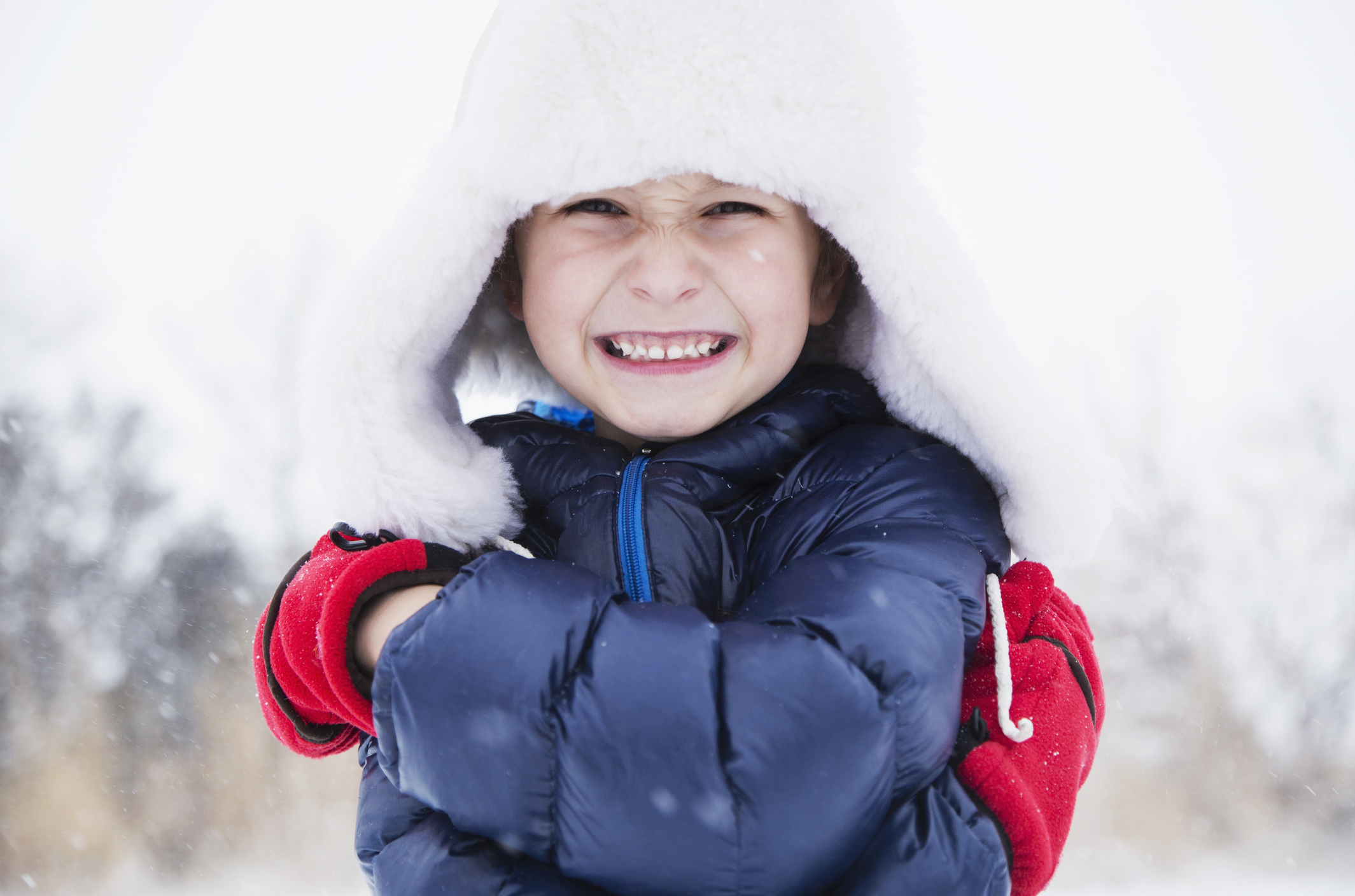 USA, Colorado, Portrait of boy (6-7) in fur hat and gloves