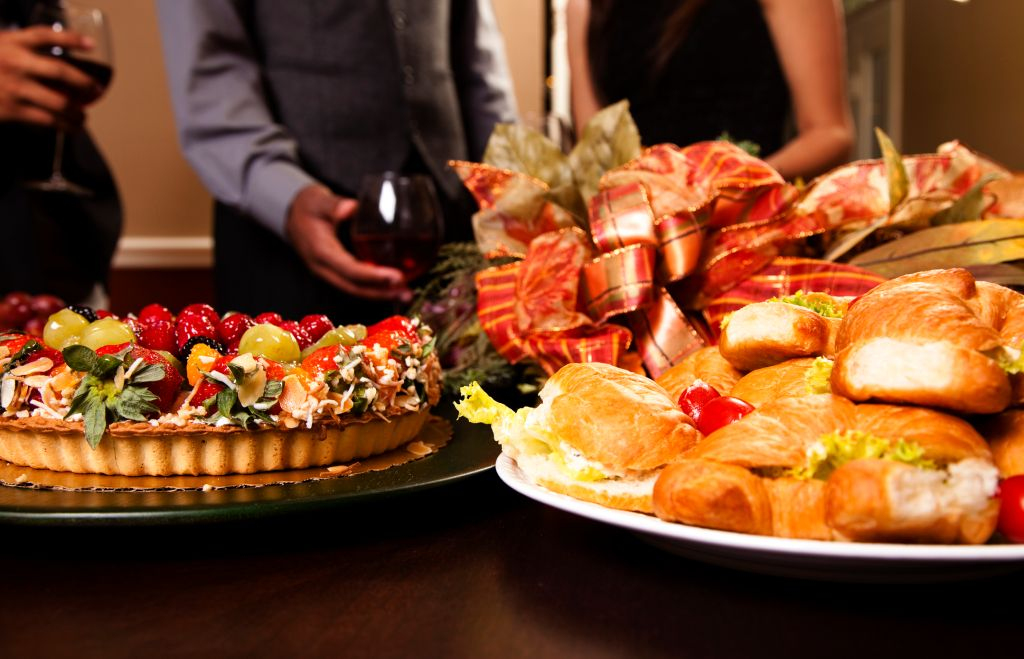 Friends sharing wine, food, appetizers. Holiday dining.