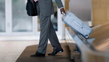 Businessman removing suitcase from luggage carousel in baggage claim