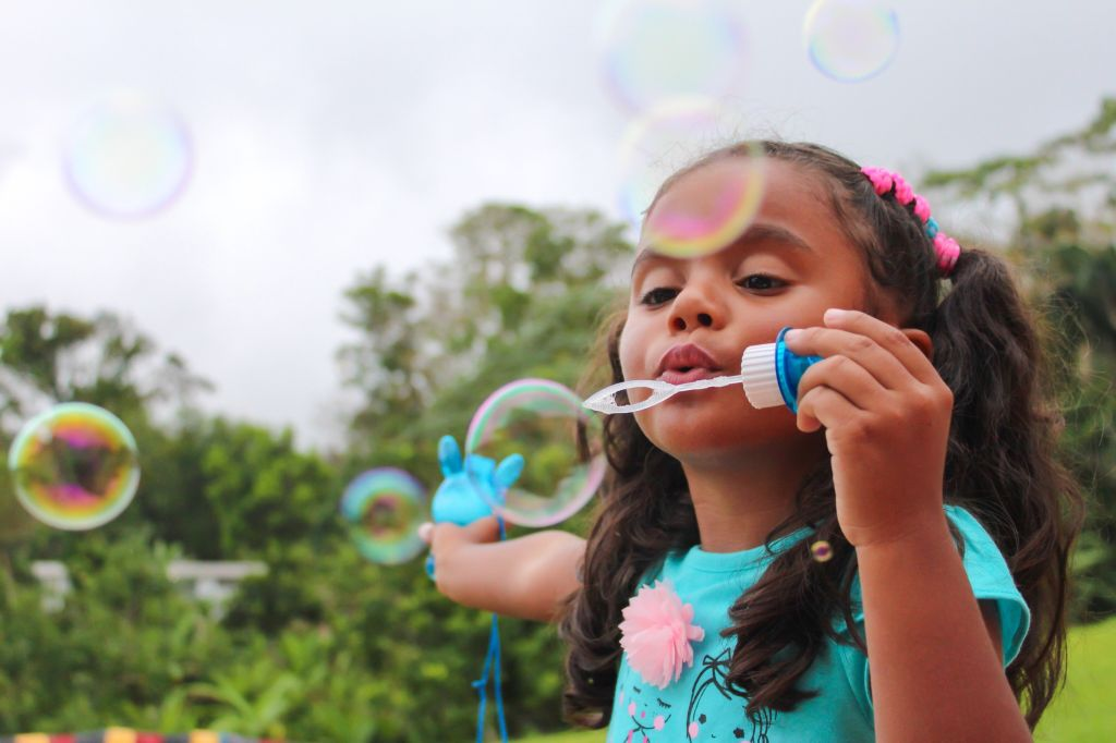 Girl Blowing Bubbles On Field Against Trees