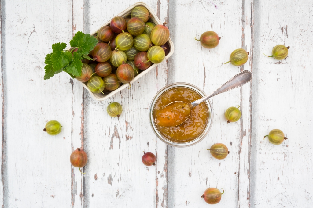 Cardboard box of gooseberries and jar of gooseberry jam on wood