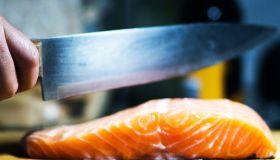 Kitchen knife cutting fresh salmon steak