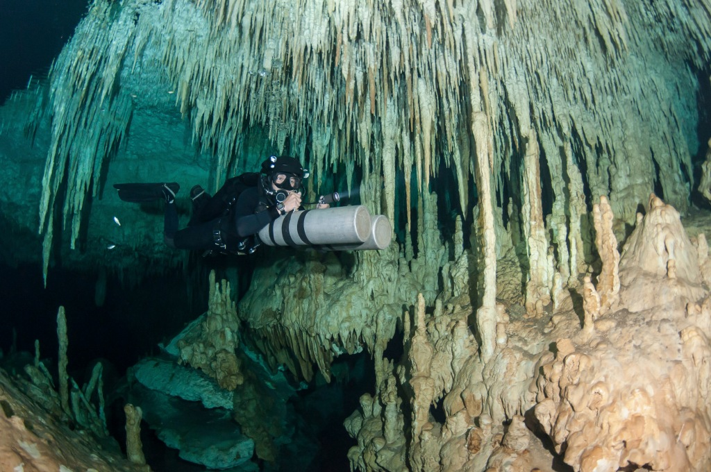 Diver using side mount gear in cave in Mexico.