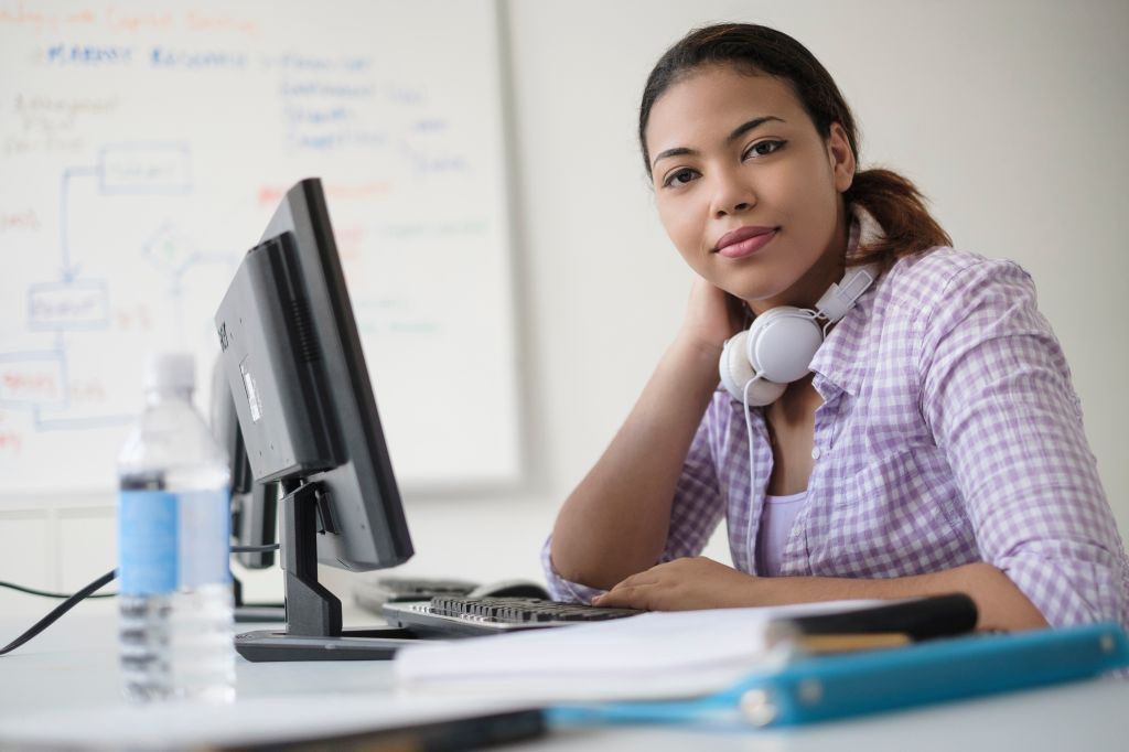 Portrait of smiling Hispanic woman in computer lab