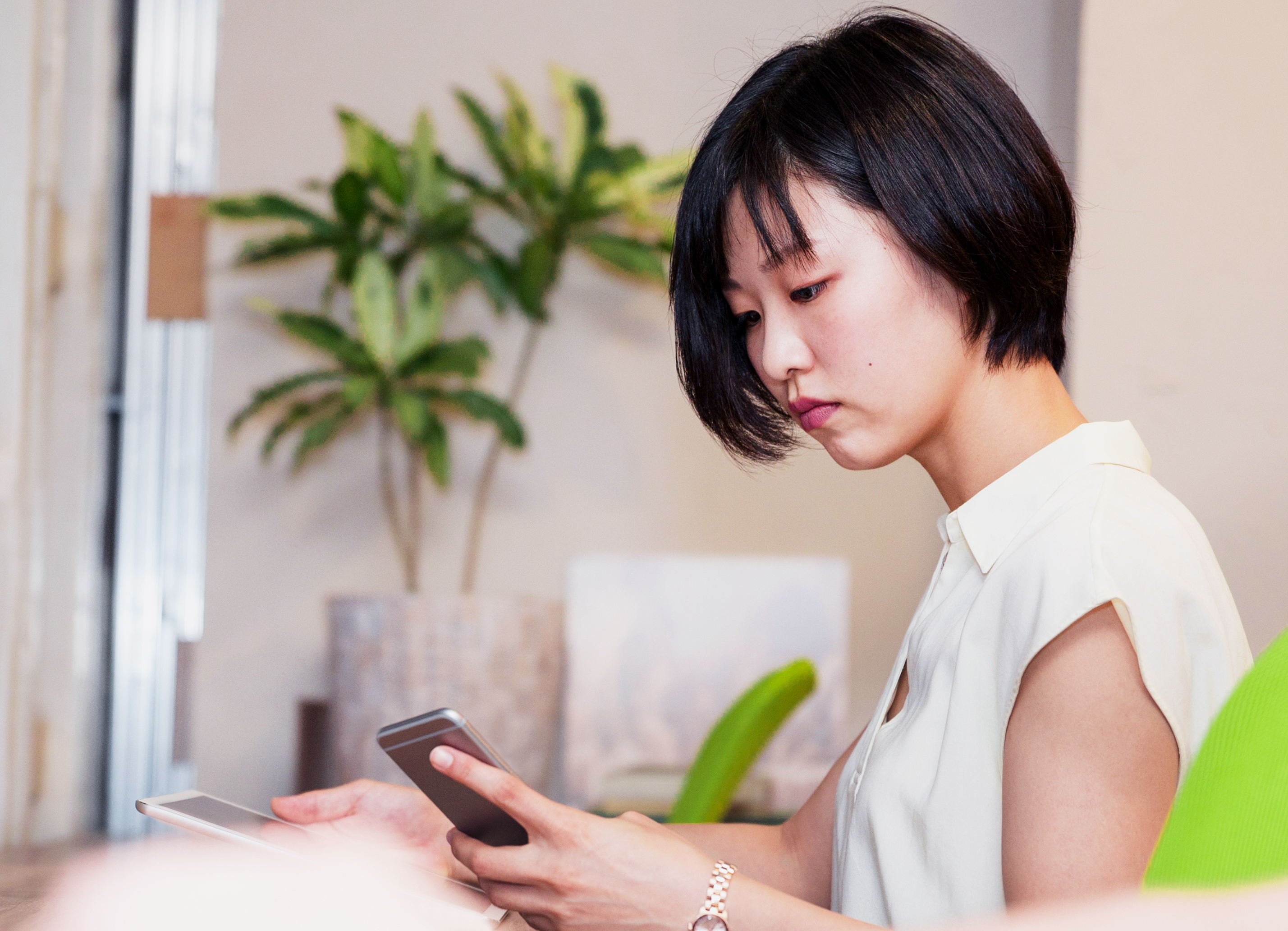 Korean businesswoman using a smartphone while also using a digital tablet