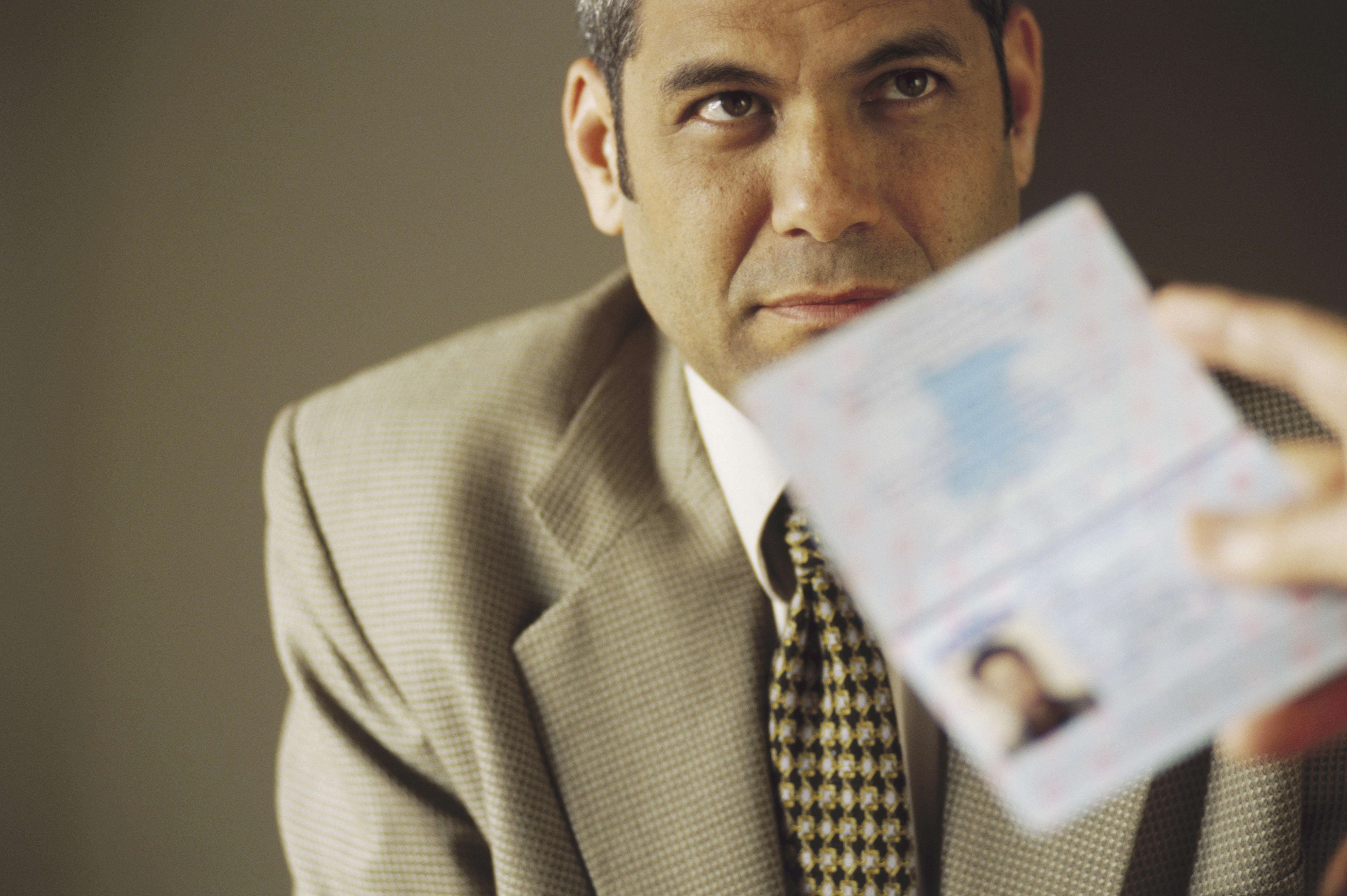 Man's Passport Being Examined