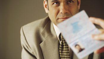 Man's Passport Being Examined
