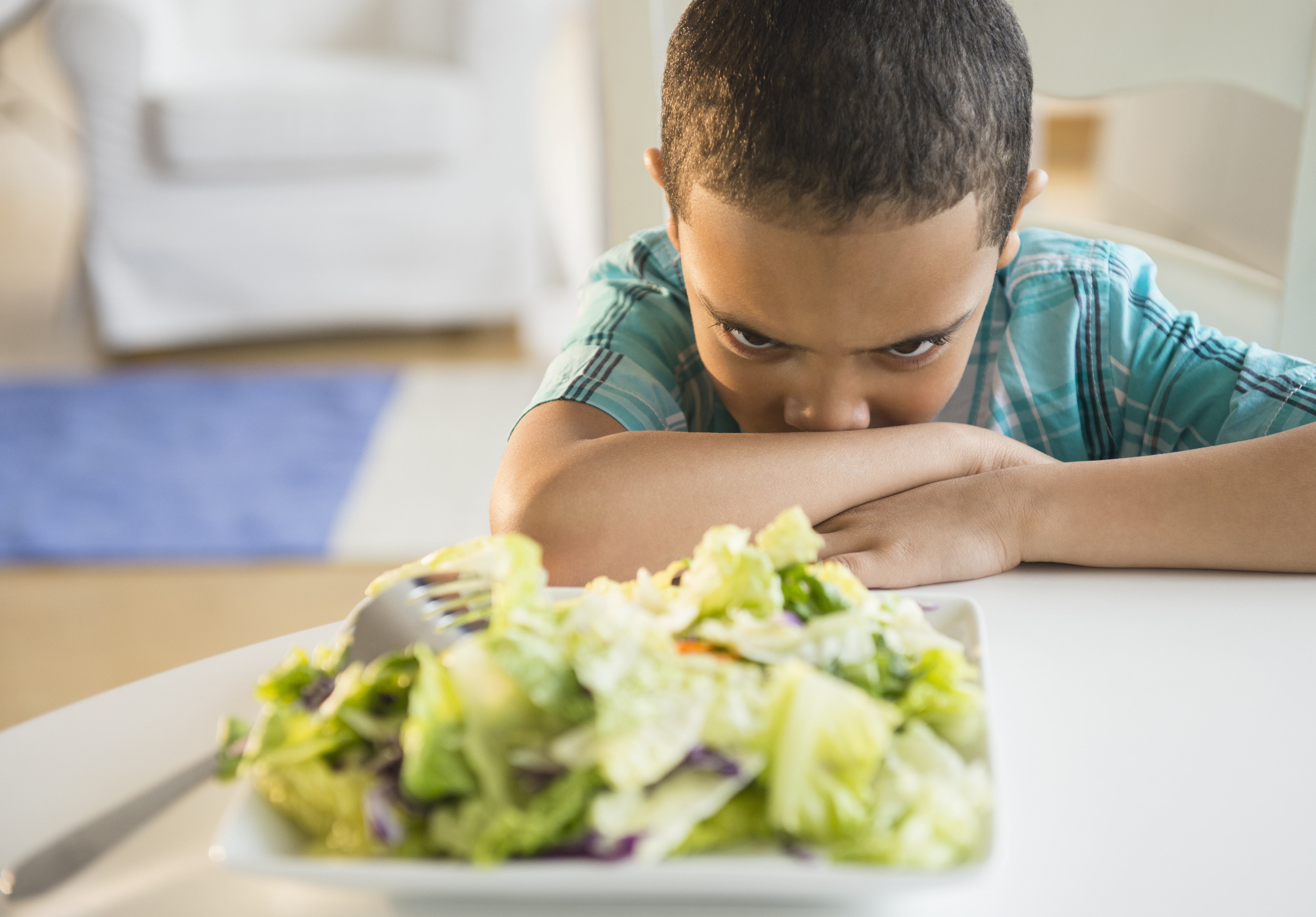 Mixed race boy refusing to eat salad