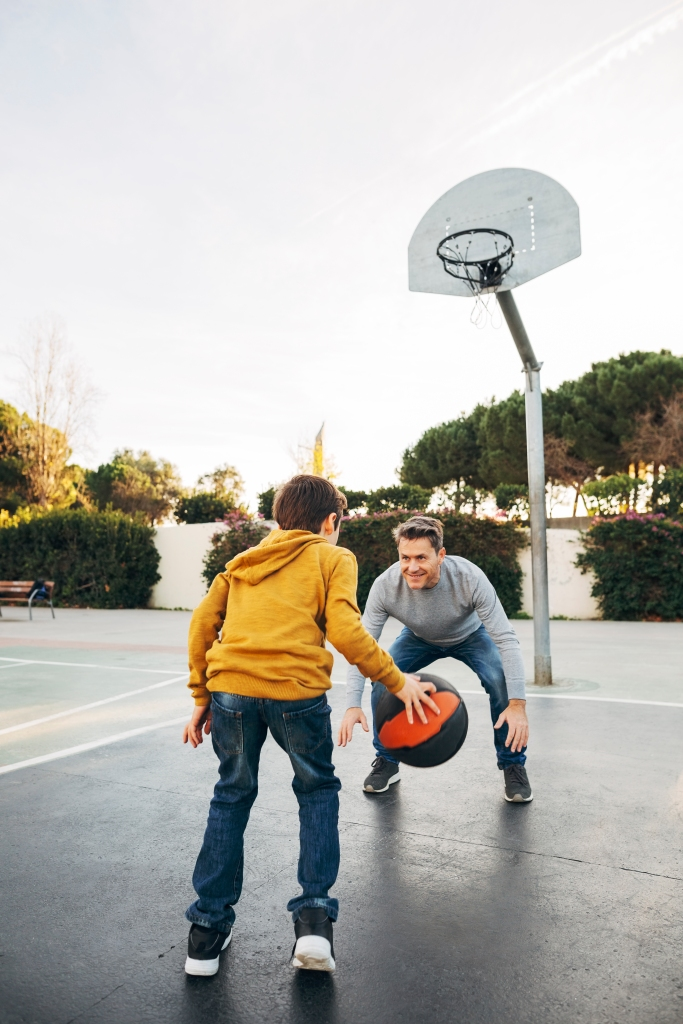 Father and son playing basketball on an outdoor court