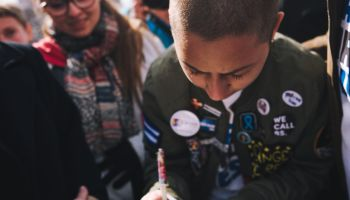 Emma Gonzalez signs a poster with Martin Luther King Jr...