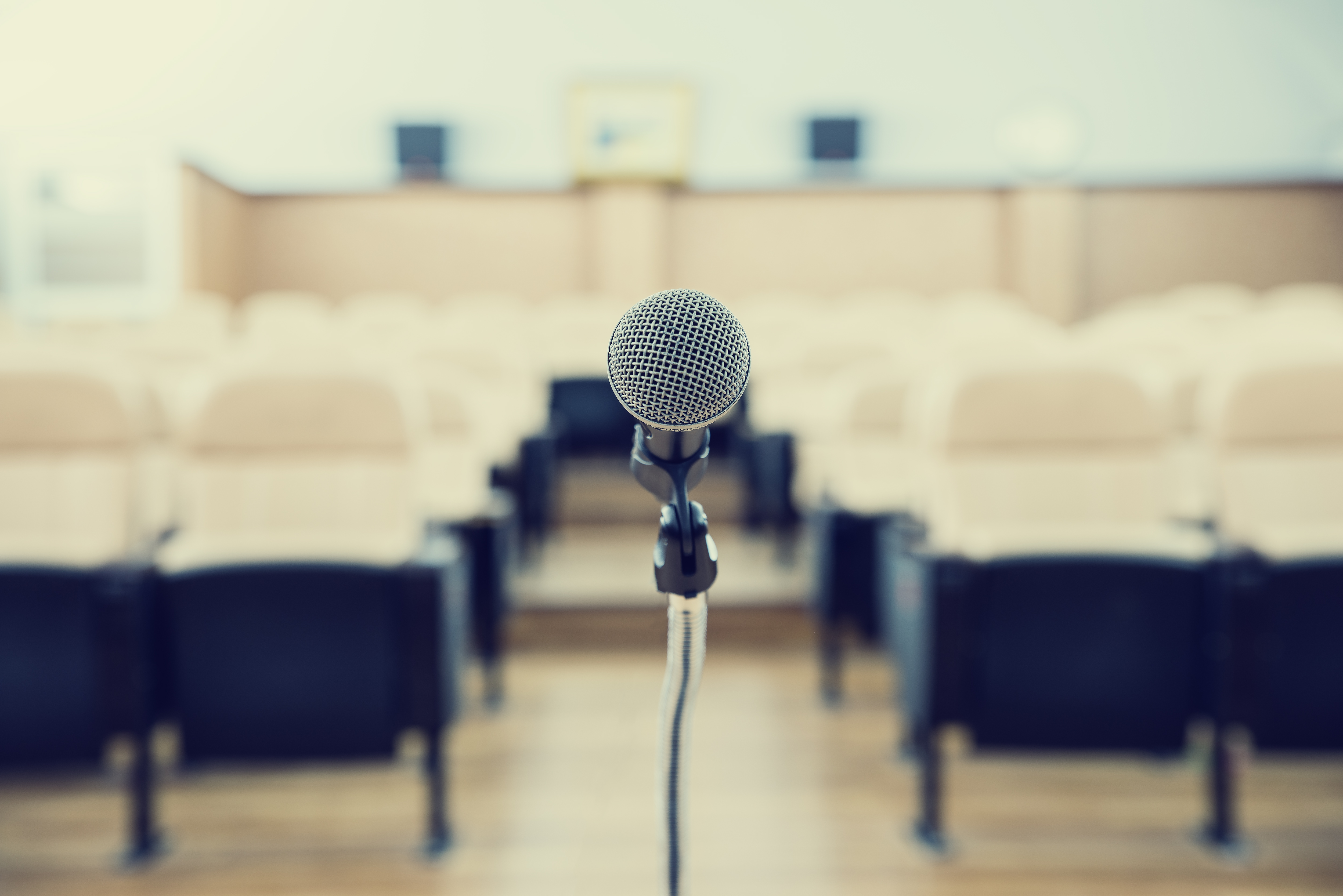 before a conference, the microphones in front of empty chairs.