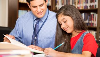 Teacher, mentor helps elementary-age schoolgirl with homework.