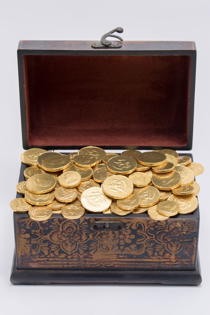 Gold Coins In Treasure Chest Against White Background