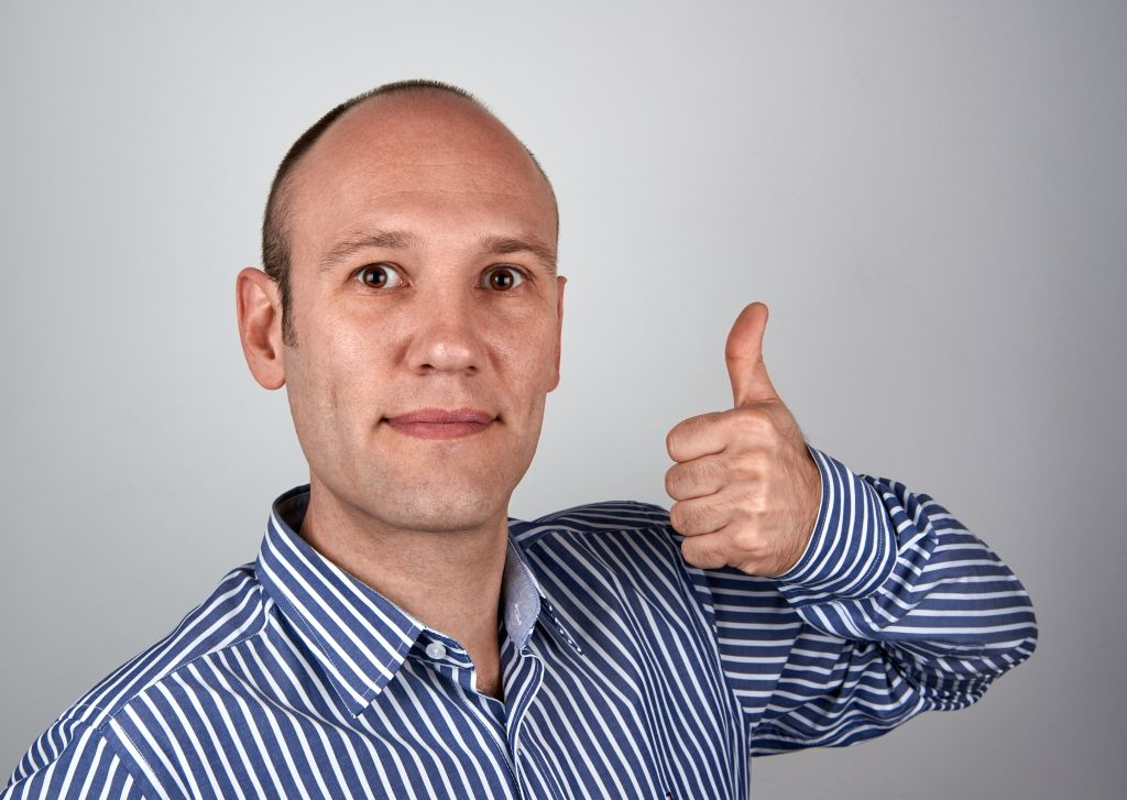 Portrait Of Mature Man Showing Thumbs Up Against Gray Background