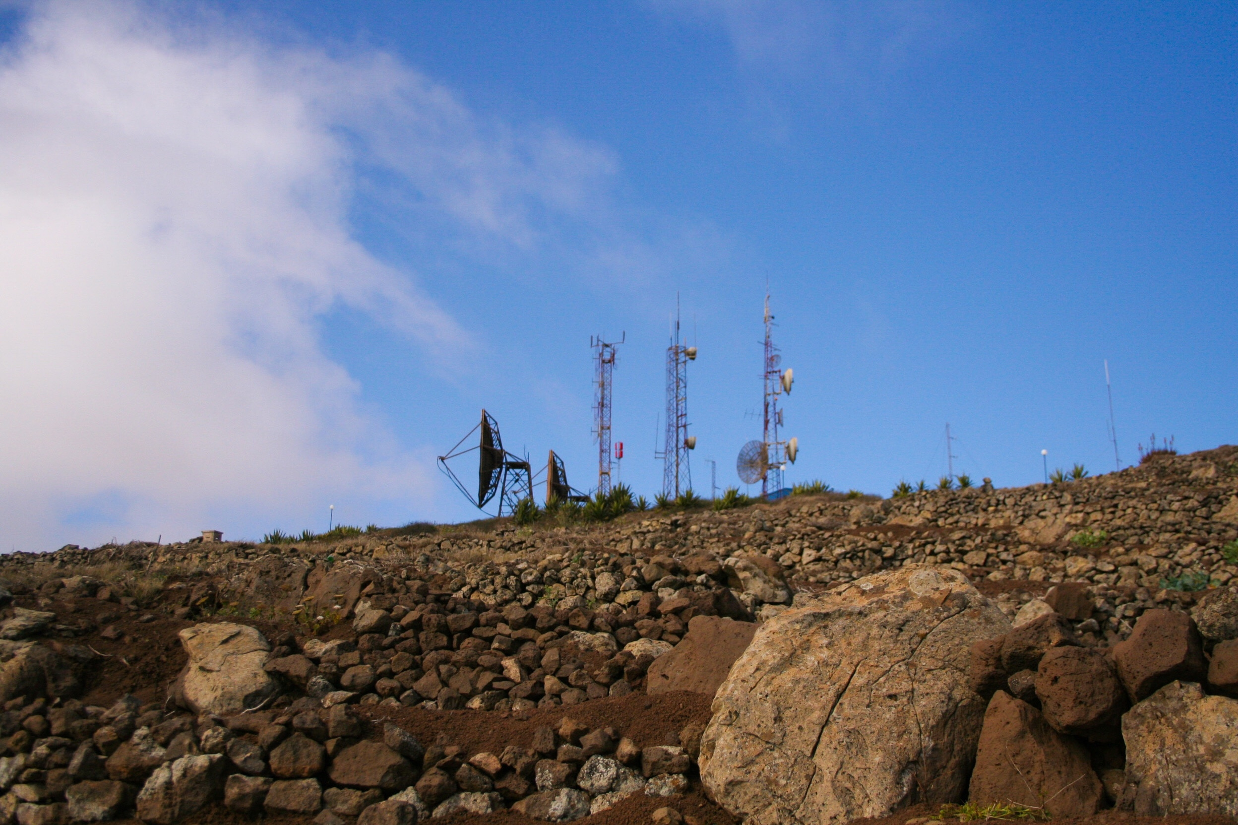 Low Angle View Of Repeater Towers And Satellite Dish On Field