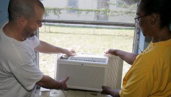 A man and woman installing an AC unit on National Rebuilding Day at Coconut Grove