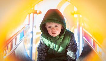 Serious Boy Sitting On Slide At Playground