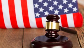 Close-Up Of Gavel With Hammer On Table Against American Flag