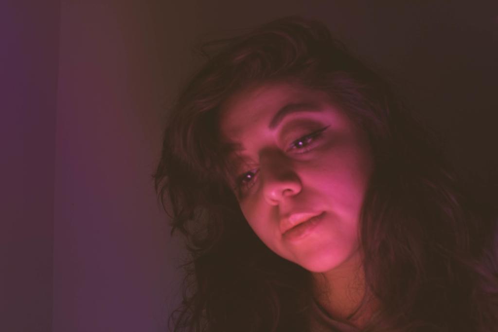 Thoughtful Woman Sitting In Darkroom