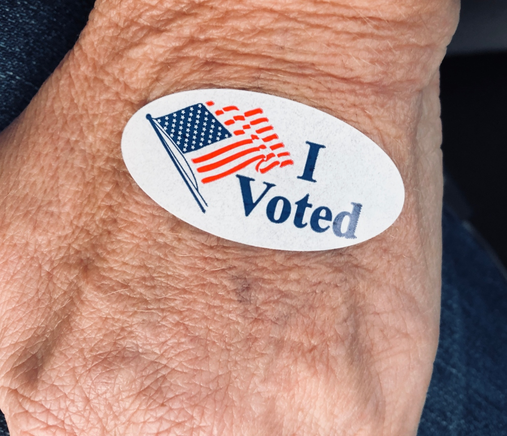 "Senior woman's hand displaying ""I voted"" sticker after early voting"