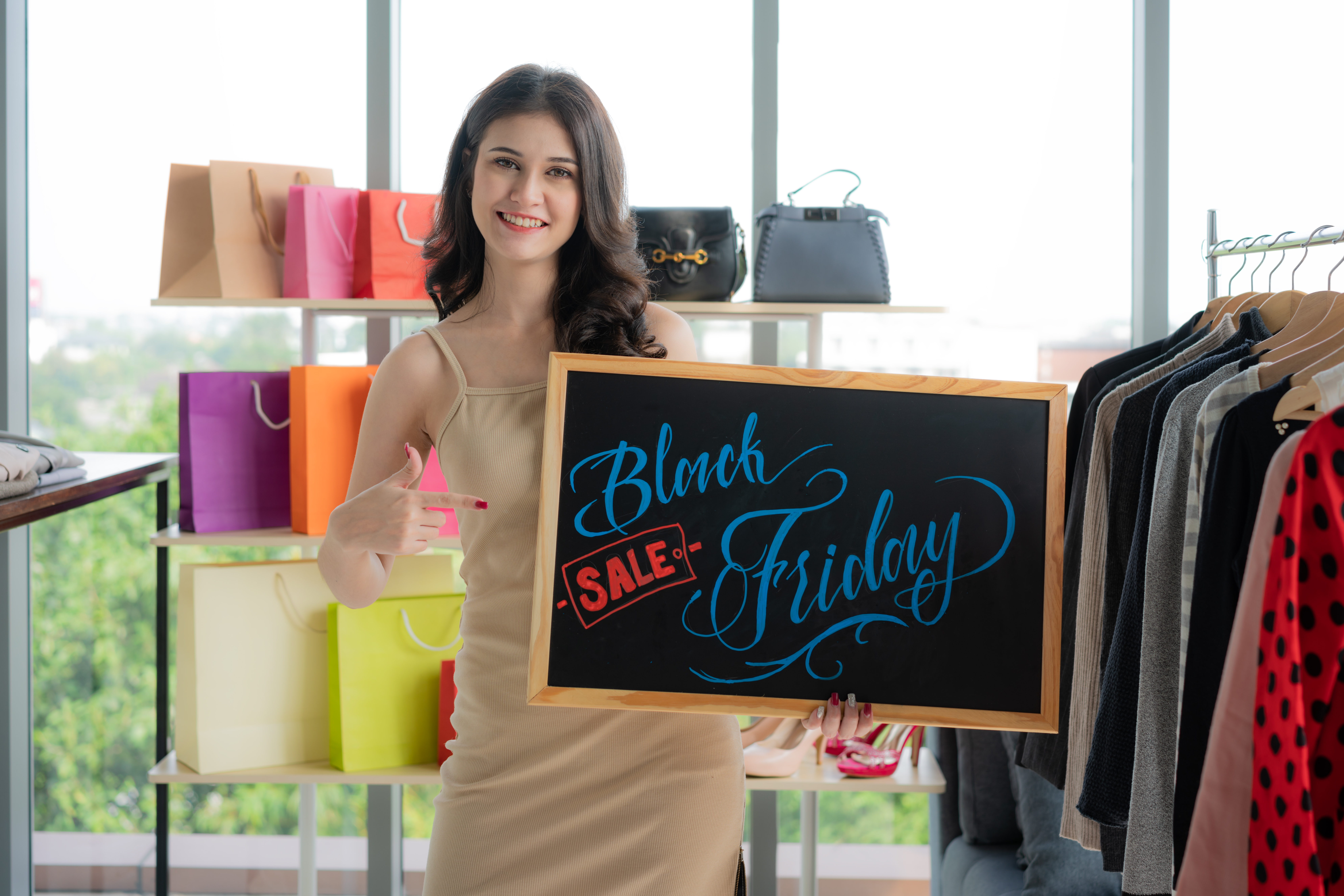 Asian woman showing Black Friday sale banner in retail shop.