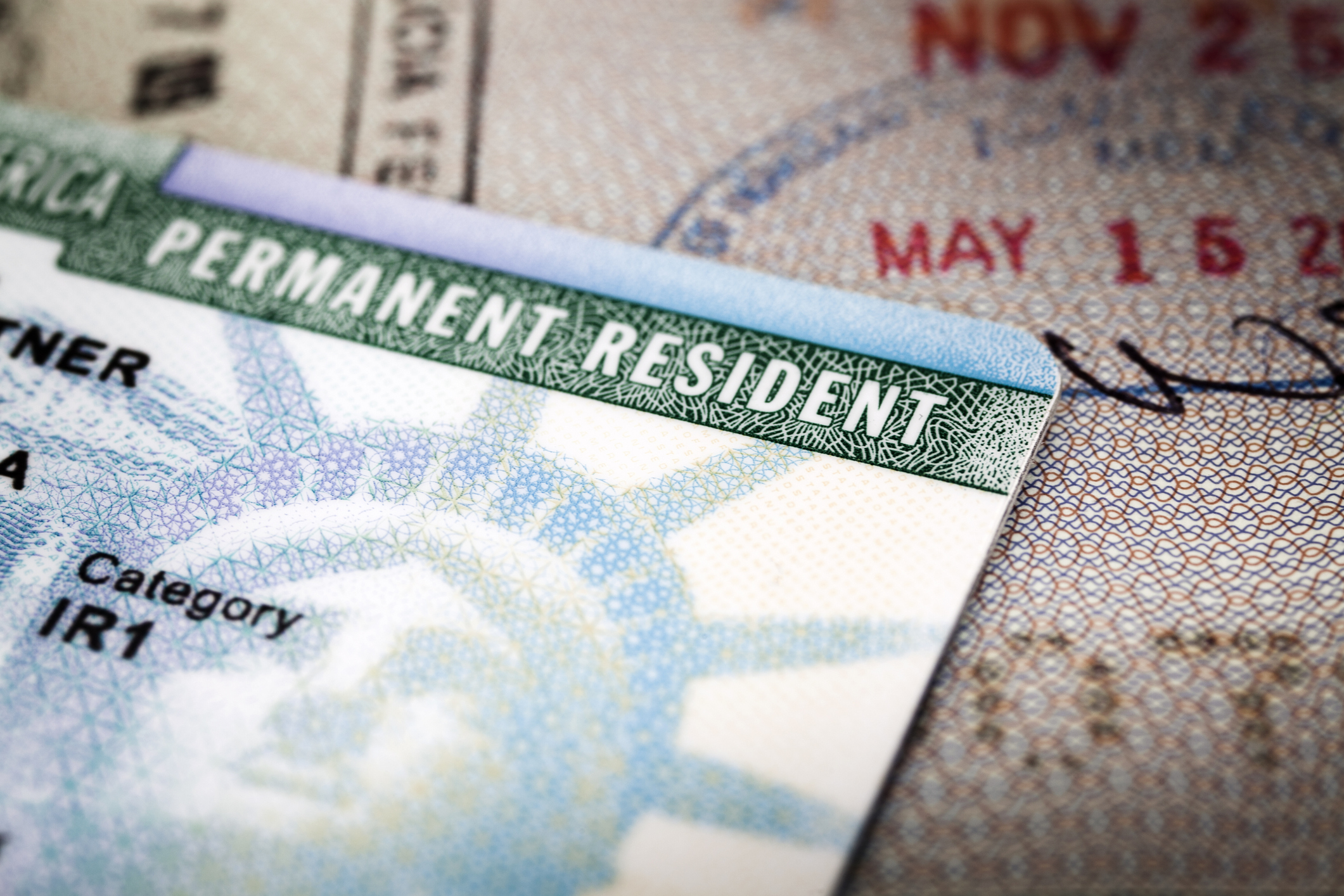 A Green Card lying on an open passport, close-up, full frame