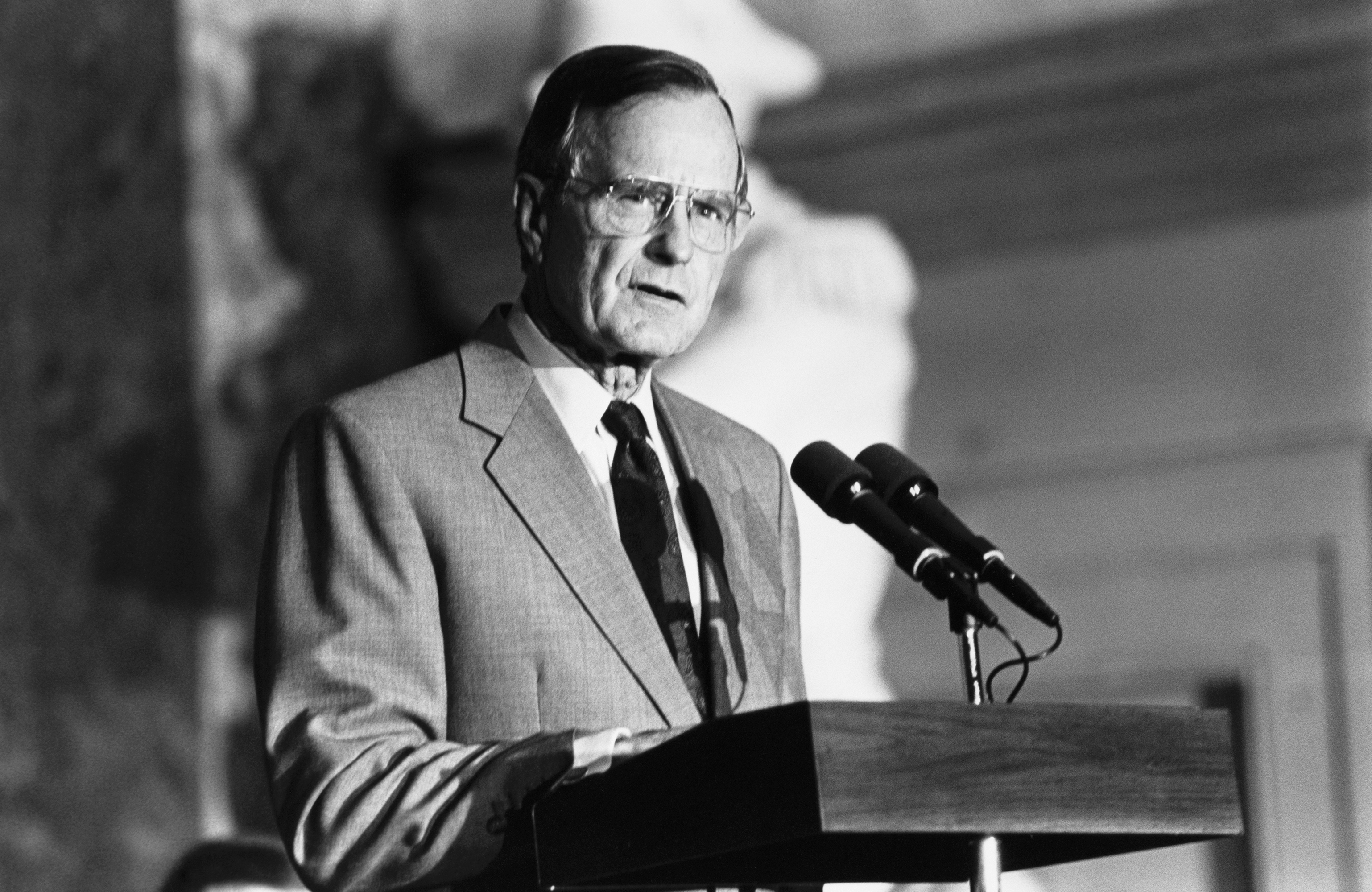George H.W. Bush talking over microphone