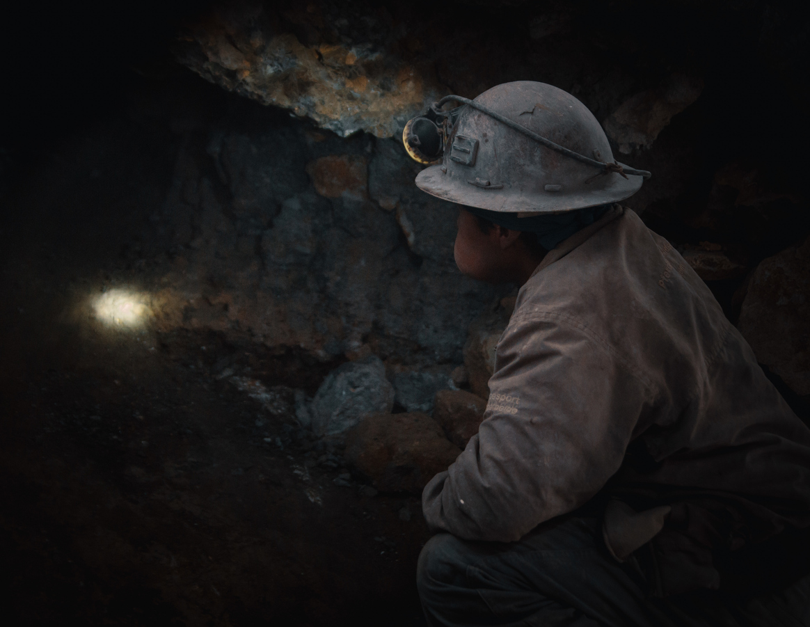 Side View Of Male Worker Crouching In Cave