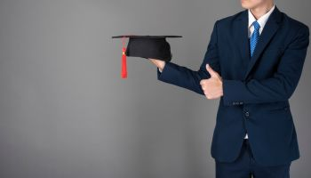 Midsection Of Businessman Holding Mortarboard Against Gray Background